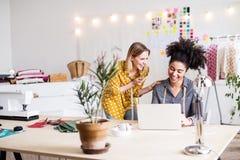 Νέες δημιουργικές γυναίκες με το lap-top στο στούντιο, επιχείρηση ξεκινήματος Στοκ Εικόνα