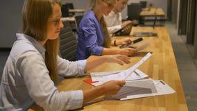 Νέες επιχειρηματίες που διαβάζουν μερικά έγγραφα που κάθονται στο γραφείο εργασίας απόθεμα βίντεο