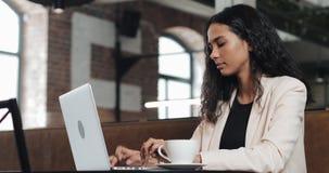 Νέες εργασίες επιχειρησιακών γυναικών για ένα lap-top στο σύγχρονο γραφείο Γελά γοητευτικά απόθεμα βίντεο