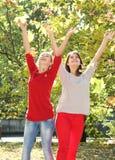 Νέες ευτυχείς γυναίκες στη φυσική ανασκόπηση φθινοπώρου Στοκ φωτογραφία με δικαίωμα ελεύθερης χρήσης