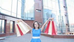 Νέες ευτυχείς τσάντες αγορών γυναικών φέρνοντας φιλμ μικρού μήκους