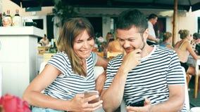 Νέες ευτυχείς φωτογραφίες προσοχής ζευγών στο έξυπνο τηλέφωνο σε έναν καφέ απόθεμα βίντεο