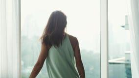 Νέες κουρτίνες ανοίγματος γυναικών brunette το πρωί Κορίτσι που κοιτάζει μέσω του παραθύρου στην άποψη πόλεων κίνηση αργή 3840x21 απόθεμα βίντεο