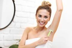 Νέες μασχάλες ξυρίσματος γυναικών στο λουτρό στοκ εικόνες