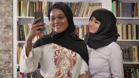 Νέες μαύρες μουσουλμανικές γυναίκες στο hijab με την άσπρη λήψη φίλων selfie στη βιβλιοθήκη, το χαμόγελο και τους ευτυχείς, ισλαμ απόθεμα βίντεο