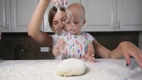 Νέες μητέρα και αυτή λίγη κόρη που προετοιμάζει τη ζύμη και που χύνει το αλεύρι στον πίνακα Baker προετοιμάζει τη ζύμη Οικογένεια απόθεμα βίντεο