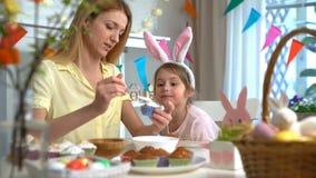 Νέες μητέρα και αυτή λίγη κόρη με τα αυτιά κουνελιών που μαγειρεύουν Πάσχα cupcakes φιλμ μικρού μήκους