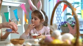 Νέες μητέρα και αυτή λίγη κόρη με τα αυτιά κουνελιών που μαγειρεύουν Πάσχα cupcakes απόθεμα βίντεο