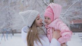 Νέες μητέρα και κόρη ευτυχείς μαζί στις χιονοπτώσεις στο πάρκο φιλμ μικρού μήκους