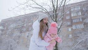 Νέες μητέρα και κόρη ευτυχείς μαζί στις χιονοπτώσεις στο πάρκο απόθεμα βίντεο