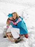 Νέες μητέρα και κόρη με ένα έλκηθρο στο χιόνι στοκ φωτογραφίες