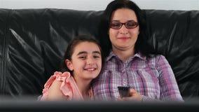 Νέες μητέρα και κόρη που προσέχουν τη TV φιλμ μικρού μήκους