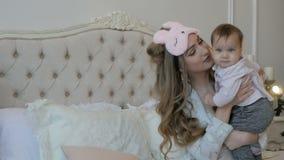 Νέες μητέρα και κόρη το πρωί του νέου έτους στο κρεβάτι στο σπίτι απόθεμα βίντεο