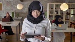 Νέες μουσουλμανικές γυναίκες στο hijab που χρησιμοποιεί την ταμπλέτα, κεκλεισμένων των θυρών, χαμόγελο, δακτυλογράφηση των επιχει απόθεμα βίντεο