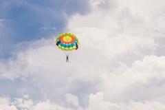 Νέες μύγες γυναικών σε ένα αλεξίπτωτο μεταξύ των σύννεφων στοκ εικόνες