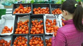 Νέες ντομάτες αγοράς γυναικών σε μια υπεραγορά απόθεμα βίντεο