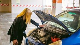 Νέες ξανθές στάσεις κοντά στο αυτοκίνητο με την αυξημένη κουκούλα διαμερισμάτων μηχανών Στοκ Εικόνες