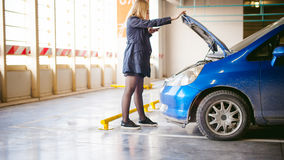 Νέες ξανθές στάσεις κοντά στο αυτοκίνητο με την αυξημένη κουκούλα διαμερισμάτων μηχανών Στοκ Εικόνα