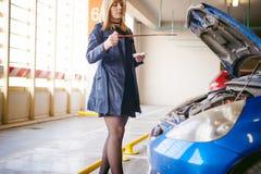 Νέες ξανθές στάσεις κοντά στο αυτοκίνητο με την αυξημένη κουκούλα διαμερισμάτων μηχανών Στοκ φωτογραφία με δικαίωμα ελεύθερης χρήσης