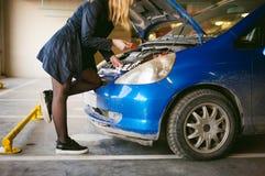 Νέες ξανθές στάσεις κοντά στο αυτοκίνητο με την αυξημένη κουκούλα διαμερισμάτων μηχανών Στοκ εικόνες με δικαίωμα ελεύθερης χρήσης