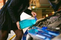 Νέες ξανθές στάσεις κοντά στο αυτοκίνητο με την αυξημένη κουκούλα διαμερισμάτων μηχανών Στοκ Φωτογραφία