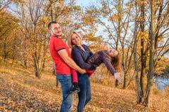 Νέες οικογενειακές στάσεις χαμόγελου στο πάρκο φθινοπώρου στοκ εικόνες