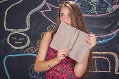 Νέες δορές κοριτσιών σπουδαστών πίσω από ένα βιβλίο Στοκ φωτογραφίες με δικαίωμα ελεύθερης χρήσης
