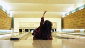 Νέες πτώσεις γυναικών κάτω ενώ ρίχνει μια σφαίρα μπόουλινγκ απόθεμα βίντεο
