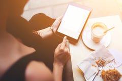 Νέες πληροφορίες ανάγνωσης κοριτσιών hipster για τον ιστοχώρο ενώ κοιτάζει βιαστικά Διαδίκτυο στο μαξιλάρι αφής στοκ εικόνα
