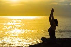 Νέες σκιαγραφιών γυναικών και γιόγκα άσκησης στο bea στοκ φωτογραφίες