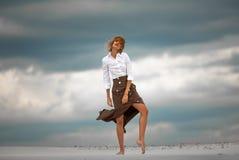 Νέες στάσεις γυναικών χωρίς παπούτσια στην έρημο στο υπόβαθρο ουρανού Στοκ φωτογραφία με δικαίωμα ελεύθερης χρήσης