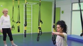 Νέες στάσεις οκλαδόν γυναικών με τις ζώνες στη γυμναστική απόθεμα βίντεο