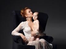 Νέες συνεδρίαση και εκμετάλλευση γυναικών μητέρων γυμνές το καλό μωρό παιδιών νηπίων της Στοκ Εικόνες