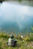 Νέες συνεδρίαση και αλιεία αγοριών Στοκ Εικόνα
