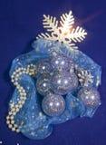 Νέες σφαίρες έτους που χύνονται τη βιολέτα στο εορταστικό ύφασμα με χρυσά snowflakes και το κόσμημα μαργαριταριών σε ένα μπλε υπό Στοκ φωτογραφία με δικαίωμα ελεύθερης χρήσης