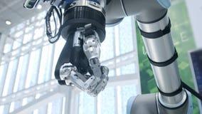 Νέες τεχνολογίες μεταξύ μας Το χέρι του ρομπότ περιστρέφεται και κινείται Συμπιέσεις και unclenches δάχτυλα Φωτεινός επιστημονικό φιλμ μικρού μήκους