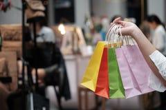 Νέες τσάντες αγορών πώλησης εκμετάλλευσης γυναικών έννοια τρόπου ζωής καταναλωτισμού στη λεωφόρο αγορών στοκ εικόνα
