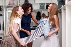 Νέες φίλες που επιλέγουν τα νέα ενδύματα που κρατούν μαζί, αξιολόγηση, που συζητά ένα φόρεμα στο κατάστημα ιματισμού στοκ εικόνες