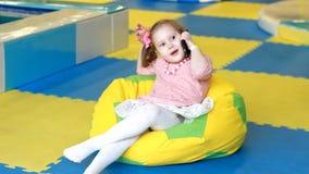 Το παιδί μιλά στο τηλέφωνο κυττάρων Παιχνίδι κοριτσάκι με το κινητό τηλέφωνο Νέες ψηφιακές τεχνολογίες στα χέρια ενός μωρού απόθεμα βίντεο