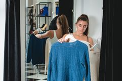Νέες όμορφες αγορές γυναικών, που πηγαίνουν στο δωμάτιο συναρμολογήσεων στη λεωφόρο μόδας, που λαμβάνει την απόφαση σχετικά με αυ στοκ εικόνα με δικαίωμα ελεύθερης χρήσης