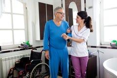 Νέες όμορφες βοήθειες νοσοκόμων στο ανώτερο άτομο στοκ φωτογραφία με δικαίωμα ελεύθερης χρήσης
