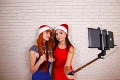 Νέες όμορφες γυναίκες στα καλύμματα Santa που έχουν τη διασκέδαση, που πίνει champag Στοκ φωτογραφία με δικαίωμα ελεύθερης χρήσης