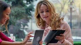 Νέες όμορφες ευτυχείς γυναίκες που χρησιμοποιούν την ταμπλέτα στον καφέ απόθεμα βίντεο