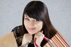 Νέες όμορφες τσάντες εγγράφου εκμετάλλευσης γυναικών χαμόγελου με τις αγορές Στοκ εικόνα με δικαίωμα ελεύθερης χρήσης