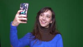 Νέες selfie-φωτογραφίες πυροβολισμού γυναικών σπουδαστών brunette smilingly στο smartphone στο πράσινο υπόβαθρο απόθεμα βίντεο