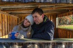 Νέοι άνδρες και γυναίκα ζευγών ομορφιάς στο αγκάλιασμα στο ξύλινο κτήριο στοκ φωτογραφίες