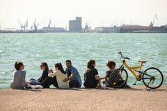 Νέοι Έλληνες που στηρίζονται στην προκυμαία στη λεωφόρο Nikis Στοκ Εικόνες