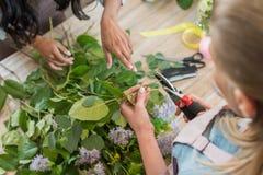 Νέοι ανθοκόμοι που τακτοποιούν τα όμορφα λουλούδια και τα πράσινα φύλλα στο ανθοπωλείο Στοκ Εικόνες
