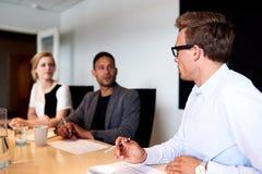 Νέοι ανώτεροι υπάλληλοι που αντιμετωπίζουν ο ένας τον άλλον κατά τη διάρκεια της συνεδρίασης Στοκ Φωτογραφία