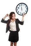 Νέοι ασιατικοί αντίχειρες επιχειρησιακών γυναικών κάτω με ένα ρολόι Στοκ φωτογραφίες με δικαίωμα ελεύθερης χρήσης